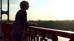 微笑的年轻人在Slo Mo享受Dnipro河的看法从桥梁的 股票视频