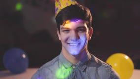 微笑的年轻人画象看在照相机的生日帽子的 不同颜色明亮的光在他的面孔的和 股票录像