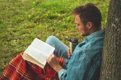 微笑的年轻人阅读书室外与温暖的红色格子花呢披肩和一杯茶背景秋天的假期和生活方式概念 库存图片