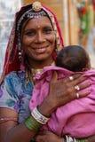 微笑的年轻吉普赛妇女和她的婴孩 库存照片