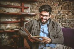 微笑的年轻商人在家放松 登记读取 免版税库存图片