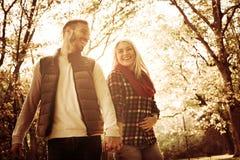 微笑的年轻夫妇在举行手和谈判的公园 库存照片