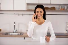微笑的年轻夫妇谈话在电话在厨房里 免版税图库摄影