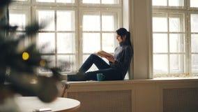 微笑的年轻女人是看书坐圣诞节和享受休息和平安的假日的窗台 股票录像