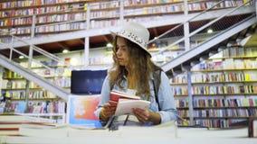 微笑的年轻女人看书在图书馆里 股票视频