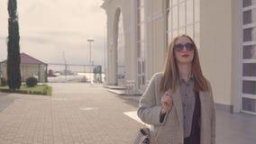 微笑的年轻女人走在街道在城市在晴朗的春日 股票录像