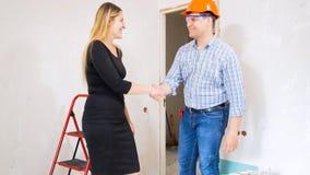 微笑的年轻女实业家与承包商握手在房子在整修下 免版税库存图片