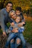 微笑的年轻家庭到叶子里在一秋天天 免版税库存照片