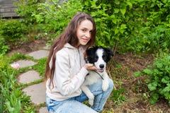 微笑的年轻有吸引力妇女拥抱huging的逗人喜爱的小狗博德牧羊犬在夏天城市公园室外背景中 免版税库存照片