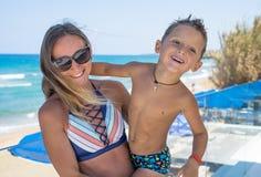 微笑的年轻母亲在海附近亲吻婴孩 几天愉快的夏天 免版税库存照片