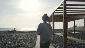 微笑的年轻浅黑肤色的男人在春天的晴朗的海滩单独跑步, 股票录像