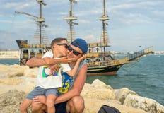 微笑的年轻父亲在日落的海附近亲吻儿子 几天愉快的夏天 友好的家庭的概念 免版税库存照片