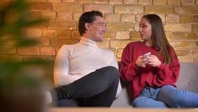 微笑的年轻白种人夫妇坐沙发观看入智能手机和谈话互相在家庭环境 股票录像