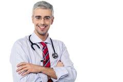 微笑的年迈的医师,横渡的胳膊 免版税库存照片