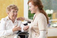 微笑的年长妇女谈话与nur的一个友好的照料者 免版税图库摄影