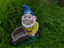 微笑的庭院变矮小与一个蓝色帽子、救生服和一辆独轮车在一个绿色草甸 库存图片