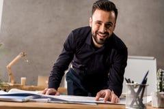 微笑的建筑师感人的图纸和看 免版税图库摄影
