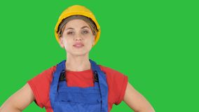 微笑的建设者工作者妇女身分和改变的姿势折叠手,在臀部的手,在口袋的手在绿色 股票录像