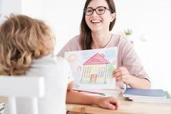 微笑的心理学家图片和孩子在家庭供应中心 免版税库存图片