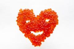 微笑的心脏由红色鱼子酱制成 库存图片