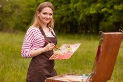微笑的快乐的女孩画象有拿着她的刷子和肮脏的调色板的长的金发的,创造杰作用启发 免版税库存照片