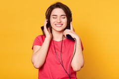 微笑的快乐的年轻女性身分被隔绝在黄色背景在演播室,闭上她的眼睛,当听到音乐,时 免版税库存图片