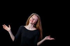 微笑的快乐的年轻棕色毛发的女孩涂了她的手对在黑背景的边 库存图片