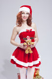微笑的性感的圣诞老人帮手女孩画象有新年礼物的 免版税库存照片