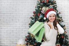 微笑的悦目白种人妇女,红色圣诞老人帽子的,举行人 免版税库存图片