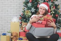微笑的悦目白种人妇女,红色圣诞老人帽子的,拥抱人 免版税库存图片