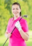 微笑的愉快女子高尔夫球运动员摆在 免版税库存图片
