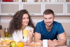 微笑的愉快的夫妇饮用的早晨咖啡  免版税库存图片