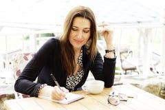 微笑的愉快的女商人做在笔记本的笔记 免版税库存图片