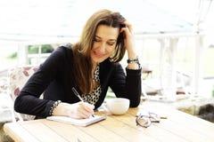 微笑的愉快的女商人做在笔记本的笔记 免版税库存照片