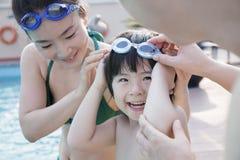 微笑的愉快的家庭帮助的儿子由游泳池边投入了风镜 库存照片