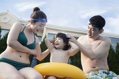 微笑的愉快的家庭帮助的儿子由游泳池边投入了风镜 免版税库存照片