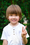 微笑的愉快的男孩画象绿色灌木的 免版税库存图片