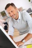 微笑的成熟人与计算机一起使用 免版税图库摄影