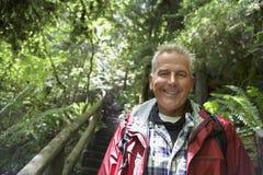 微笑的成熟人在森林里 免版税库存图片