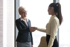 微笑的成熟女实业家握手年轻雇员congratula 库存图片