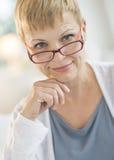 微笑的成熟妇女佩带的镜片 免版税库存照片