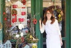 微笑的成熟妇女卖花人在花店 库存照片