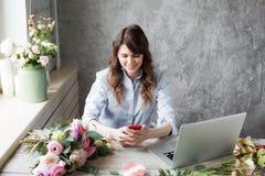 微笑的成熟妇女卖花人小企业花店所有者 她使用她的电话和膝上型计算机接受命令为 图库摄影