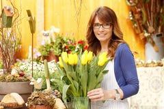 微笑的成熟妇女卖花人小企业花店所有者 库存图片
