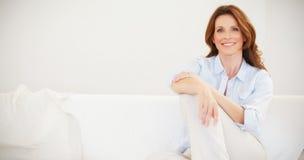 微笑的成熟妇女坐沙发 免版税库存图片