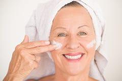 微笑的成熟妇女面孔护肤 免版税库存照片