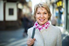 微笑的成熟白肤金发的妇女画象在镇里 免版税库存照片
