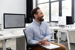微笑的成熟的商业供以人员拿着手机和笔记薄 免版税库存照片