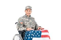 微笑的战士画象轮椅的有看照相机的美国国旗的 库存照片