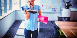 微笑的执行委员谈话在手机,当拿着锻炼席子和鞋子时 图库摄影